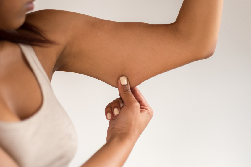 Close up Conscious Young African-American Woman Holding Excess Fat on her Arm Against White Wall Background.